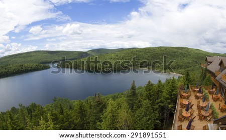 wooden terrace facing a lake in the middle of the forest - stock photo