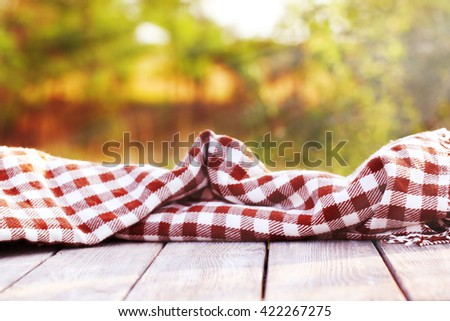 Wooden terrace with blanket against bright background - stock photo