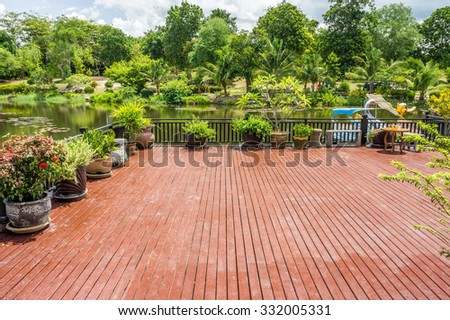 Wooden terrace with pond and garden. The design of exterior decoration.