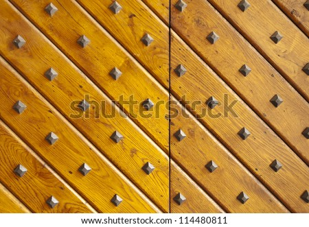 Wooden texture with nails. Ancient wooden gate door.