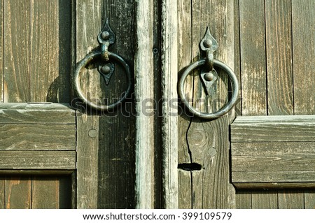 Wooden textured door with keyhole and worn iron door handles in the form of ring. Architectural detailed background. Vintage filter applied - stock photo