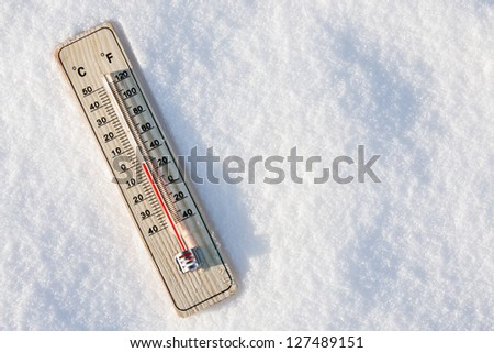 wooden thermometer in the snow with zero temperature - stock photo