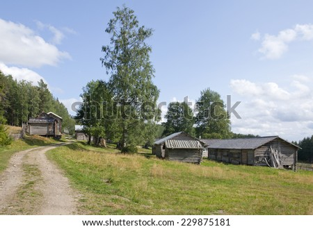 Wooden timber buildings in sunny afternoon. Gravel road crosses the small village on the slope. Farmland this side, forest in the background. - stock photo