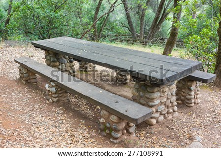 Wooden topped rustic picnic tables sit in American state park land. - stock photo