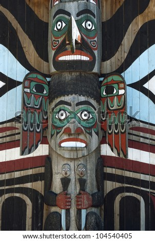 Wooden totem pole, monumental sculpture carved from large tree - stock photo