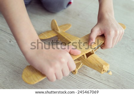 Wooden toy airplane in hands held by child - stock photo