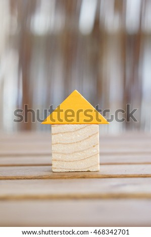 Wooden toy blocks in house shape with orange roof on table