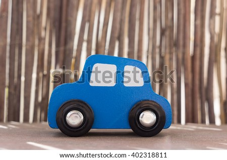 Wooden toy car on wooden shelf - stock photo