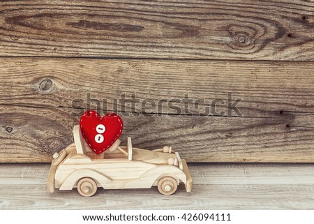 Wooden toy car with a heart on a background of old boards. Place for text.  - stock photo