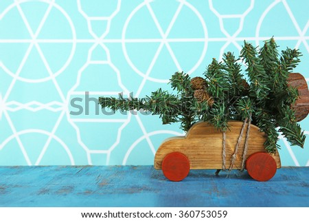 Wooden toy car with Christmas tree on a table over pattern background - stock photo
