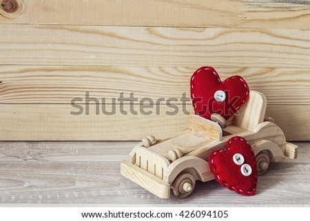 Wooden toy car with red hearts on a background of wooden  boards. Place for text.  - stock photo