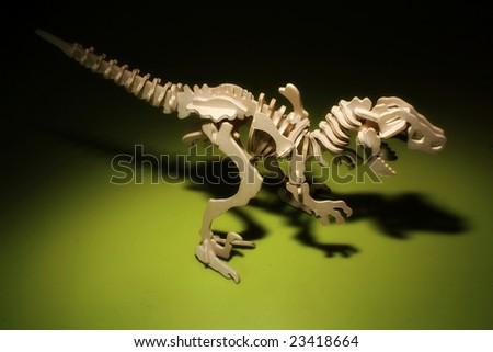 Wooden toy Dinosaur Skeleton on Black green background - stock photo