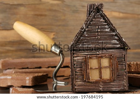 Wooden toy house on trowel and tiles on wooden background, close up