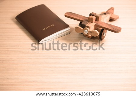 Wooden toy plane and the passport with copy space. Travel concept - stock photo