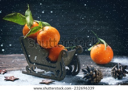 Wooden toy sled with tangerines over wooden background with snow and cone. - stock photo