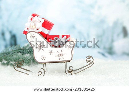 Wooden toy sledge with Christmas gifts  on nature background - stock photo