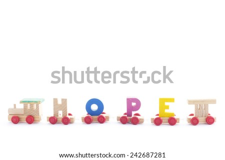 Wooden toy train carrying text for HOPE on white background. - stock photo