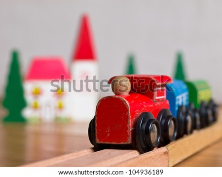 Wooden toy train with village and bridge in backdrop - stock photo