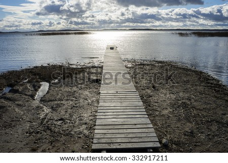 wooden trail to the lake - stock photo