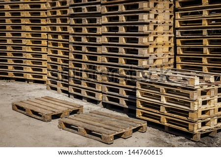 Wooden transport pallets in stacks ready for delivery. Two palettes in the foreground.  - stock photo