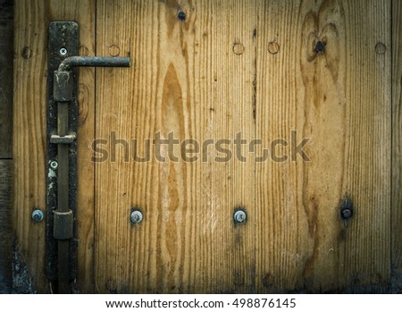 Wooden trapdoor with an iron latch - Latch and wooden planks, part of an aged door from a german warehouse, with copy space on the right side for your text.