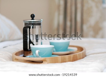 Wooden tray on the bed prepared for serving the breakfast - stock photo