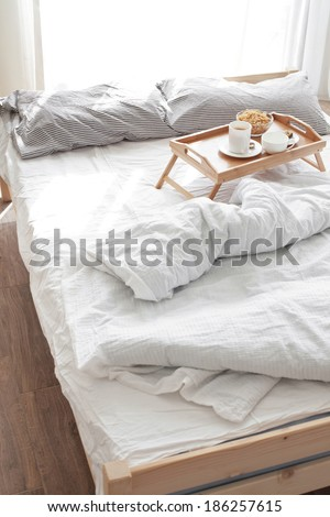 Wooden tray with coffee and breakfast on the bed - stock photo