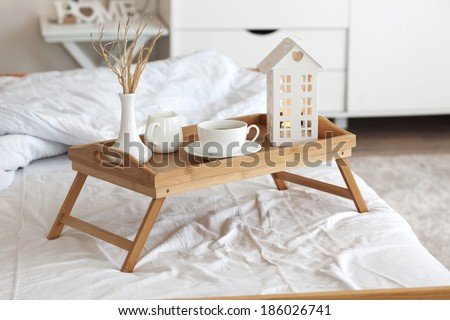Wooden tray with coffee and interior decor on the bed with white linen - stock photo