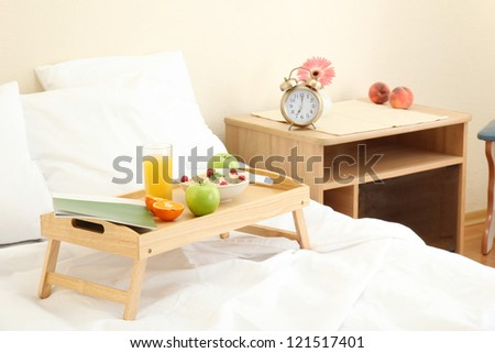 wooden tray with light breakfast on bed - stock photo