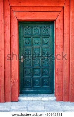 Wooden turquoise door with red doorjamb. - stock photo