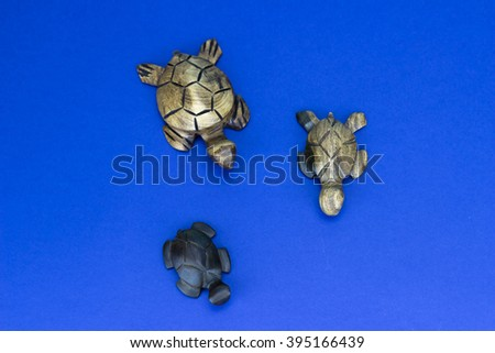Wooden turtle figurines on blue background - stock photo