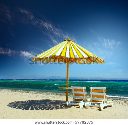 Wooden umbrella on a beach and two chairs