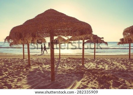 Wooden umbrellas in a beautiful beach at summer sunset. Soft and warm tones edition. - stock photo