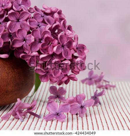 Wooden vase with a bouquet of purple lilac spring flowers on textured background - stock photo