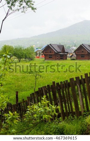 Wooden village houses with tile roofs. Wooden fence on the foreground and high mountain surrounded by mist on the background