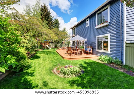 Wooden walkout deck in the backyard garden of blue siding house. Furnished with patio table set with umbrella - stock photo