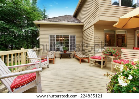 Wooden walkout deck with many deck chairs - stock photo