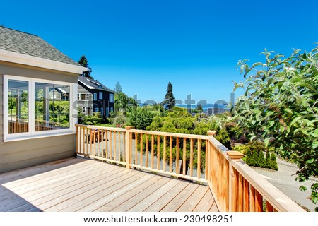 Wooden walkout deck with railings. Deck overlooking driveway and neighborhood - stock photo