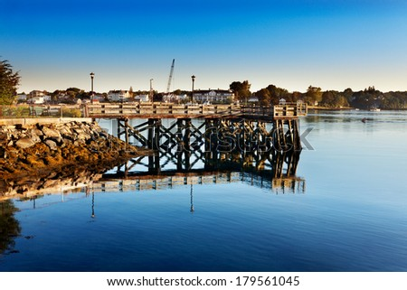Wooden walkway juts into the swift Piscataqua River early on a summer morning, Portsmouth, New Hampshire - stock photo