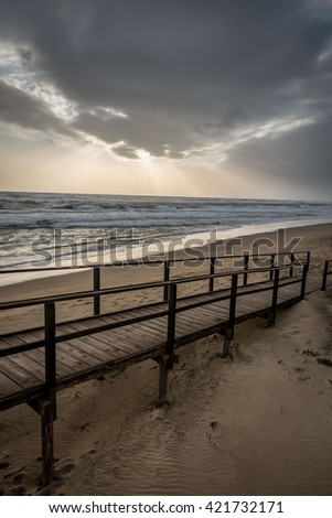 wooden walkway on the beach at sunset with clouds in the sky - stock photo