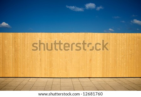 wooden wall and a blue sky next to a walk way. background image. - stock photo