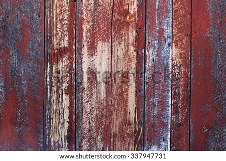 wooden wall background with faded red paint. - stock photo