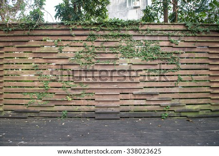 Wooden wall background with green grass - stock photo