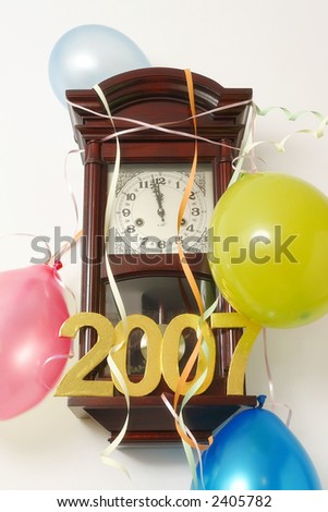 Wooden wall clock decorated with streamers and balloons indicating almost 12 p.m. hour on New Year's Eve - stock photo