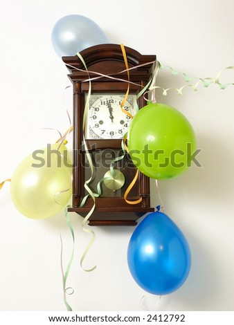 Wooden wall clock decorated with streamers and balloons indicating 2 minutes to 12 p.m. hour on New Year's Eve - stock photo