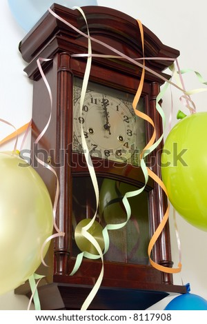 Wooden wall clock decorated with streamers and balloons showing almost 12 p.m. time of New Year's Day - stock photo