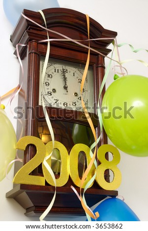 Wooden wall clock decorated with streamers, balloons and 2008 year figures showing almost New Year time - stock photo