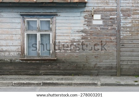 Wooden wall of the old house with a window, a sign and the asphalt road before it as background.
