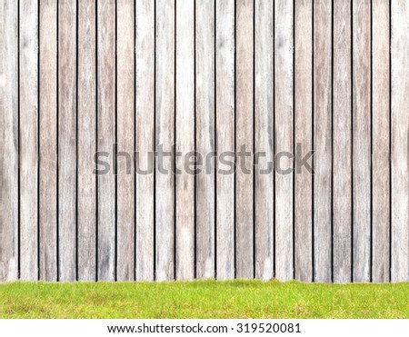 wooden wall on green field background - stock photo