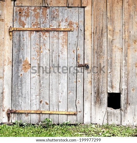 wooden wall with a door and hole for the dog - stock photo